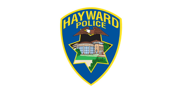 Hayward Police Logo in the shape of a blue badge with Hayward Police written across the top in yellow. An illustration of a Bald Eagle over an illustration of City Hall in the shape of a 7-point star is in the middle.