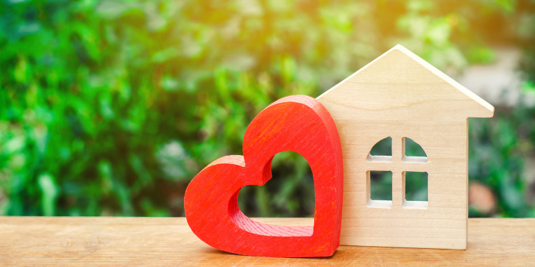 Photo of a small wooden house figurine next to a red wooden heart figurine on a wooden table.