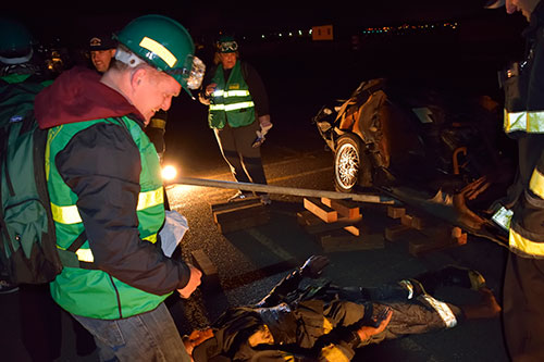 People in green CERT vests working a night simulation of a car crash