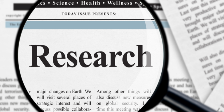 A newspaper with a magnify glass focused on the word research