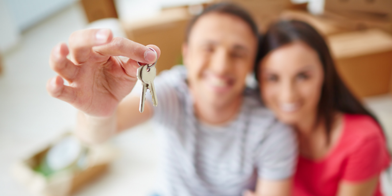 A couple smiling holding house keys