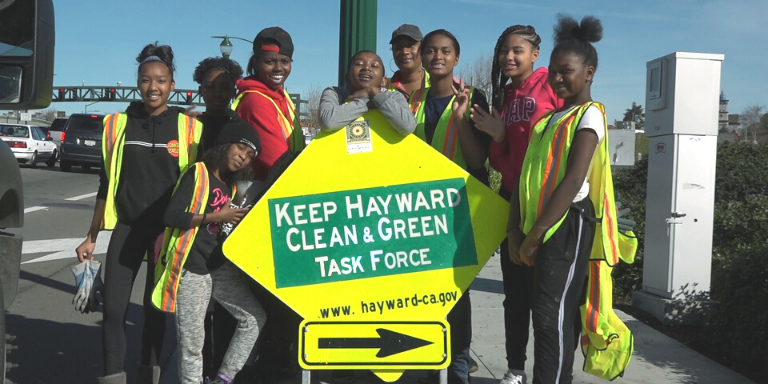 a group of young people in yellow task force vests posing behind a Keep Hayward Clean and Green Sign