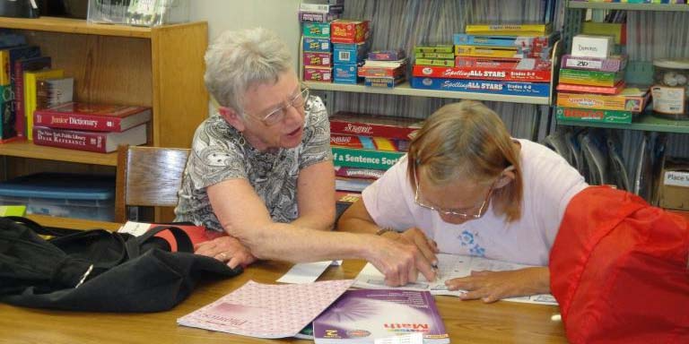 A tutor and an adult student reading together