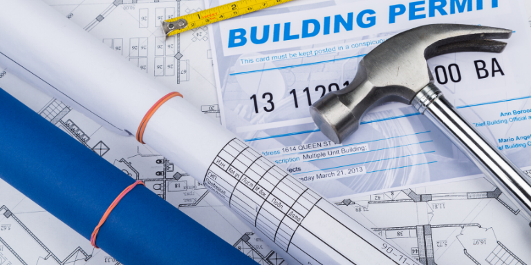 A hammer on top of a building permit next to two sets of rolled up plans