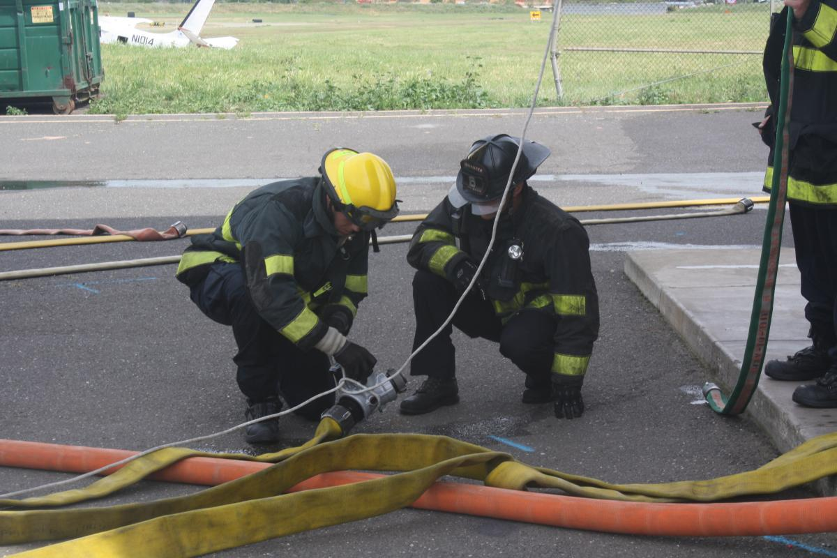 Fire fighter recruits in full turnout gear practice putting hoses together