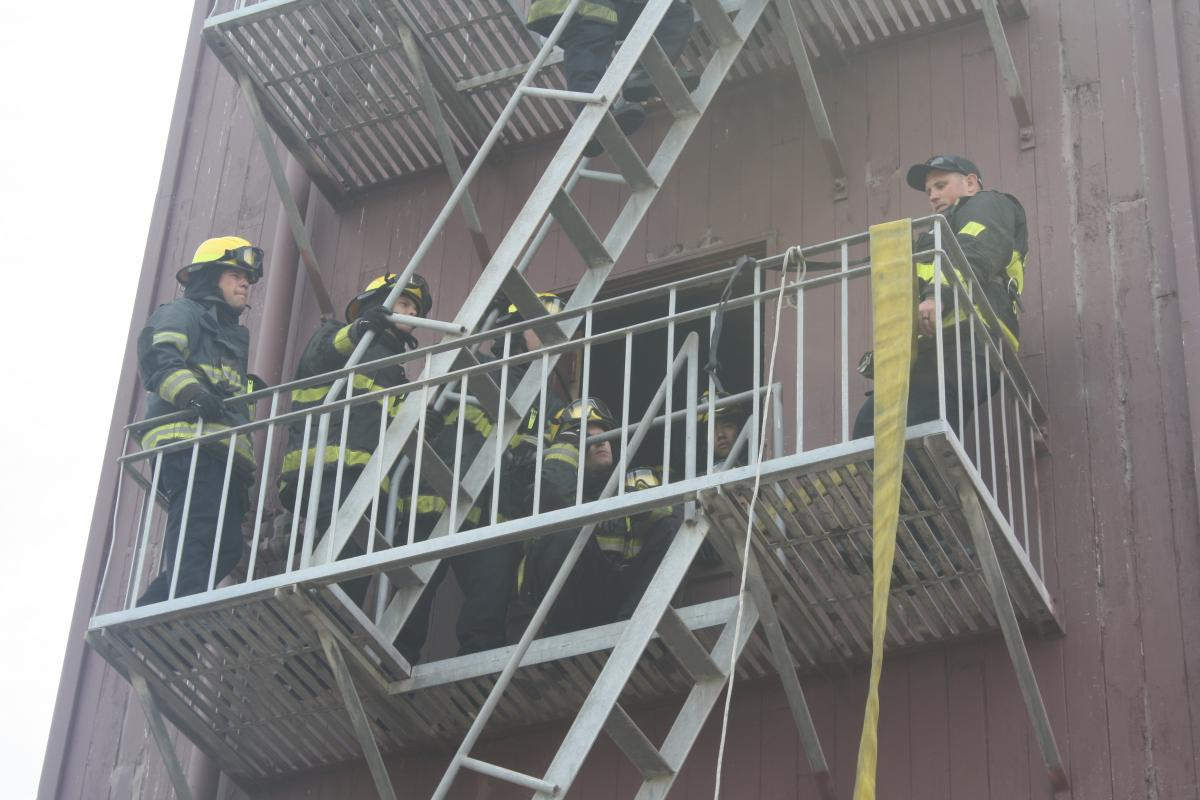 fire fighter recruits in full turnout gear going up a fire escape on a training building