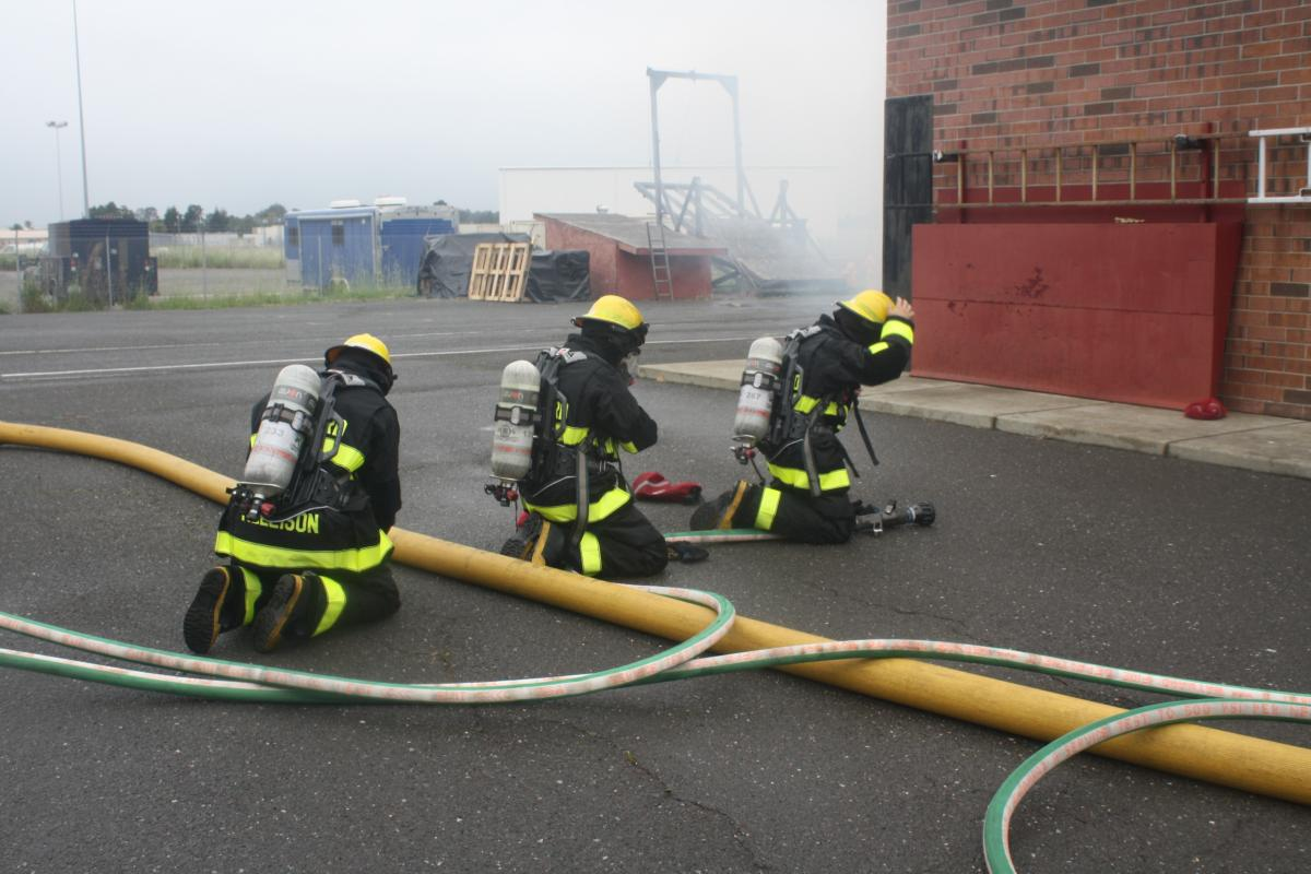Fire fighter recruits in full turnout gear work with hoses out side of the training building