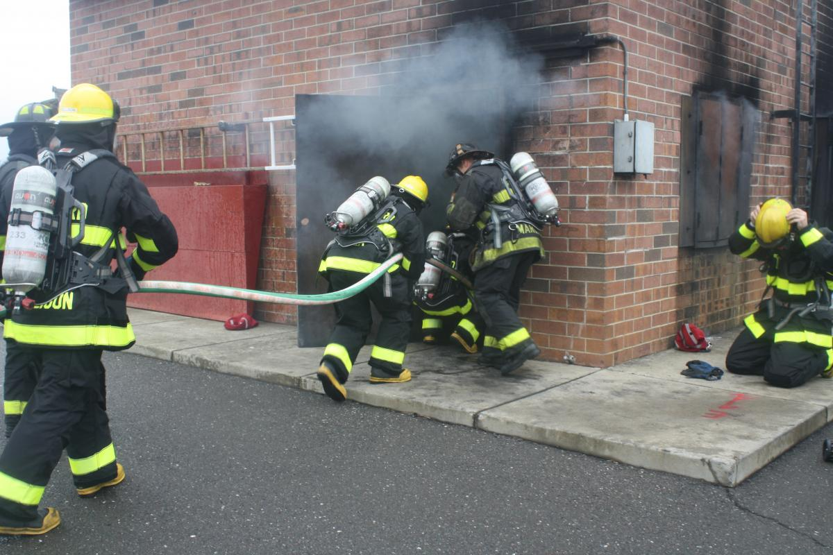 Fire fighter recruits working with fire fighters to enter the training building