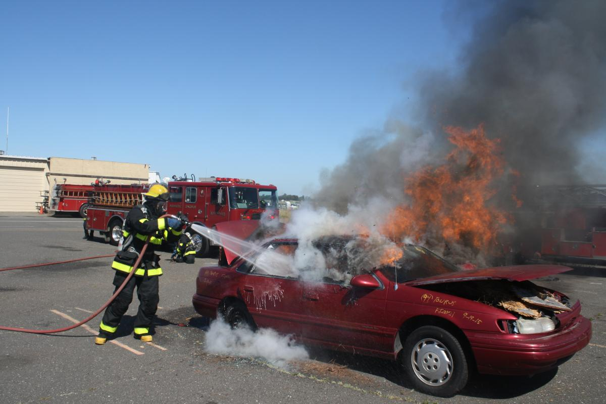 A fire fighter recruit in full turnout gear practices extinguishing a car fire