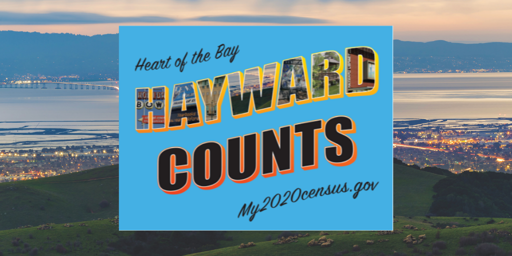A blue Hayward Counts 2020 Census sign on top of a image of the Hayward skyline