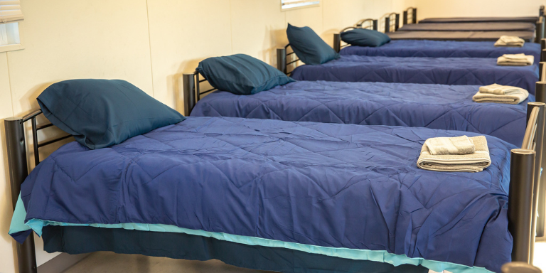 a row of blue beds lined up at the Navigation Center