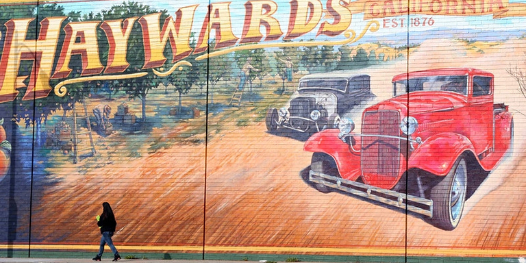 three old cars racing down a dirt path surrounded by orchards. Greetings from Haywards California written across the top
