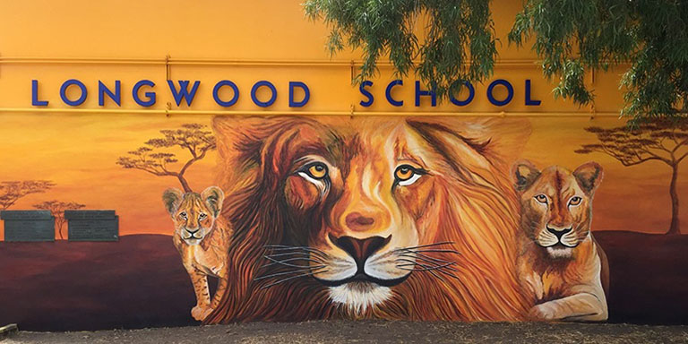 Yellow building with blue letters spelling out Longwood Elementary School. Beneath that are the faces of three lions