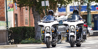 Two police officers riding motorcycles down the street