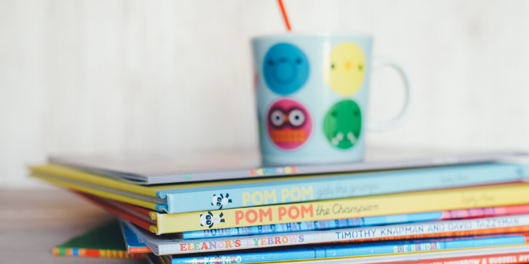 A stack of colorful books with a cup on top