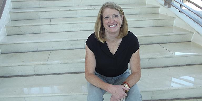 Kelly McAdoo sitting on white marble stairs smiling at the camera