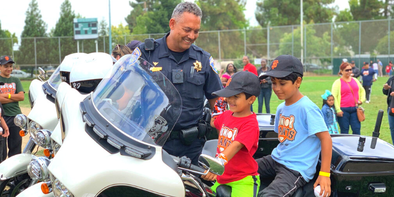 A police officer showing his motorcycle to two Jr. Giants players