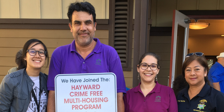 people standing with a crime free multi housing sign