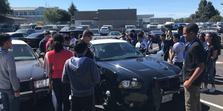 Young people looking at a black and white police car