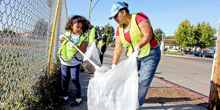 a woman and a child picking up trash