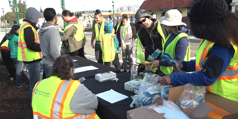 Men and women in yellow Keep Hayward Clean and Green vests getting ready for a cleanup event
