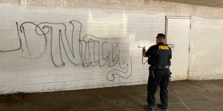 a police officer painting over graffiti