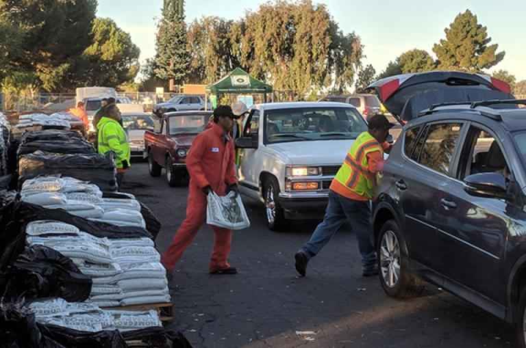 Hayward staff loading compost into Hayward resident cars