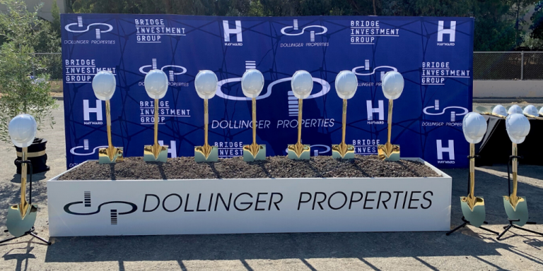 Gold shovels and white hard hats propped up in dirt in front of a blue sign with white Hayward, Dollinger Properties and Bridge Investment Group logos.