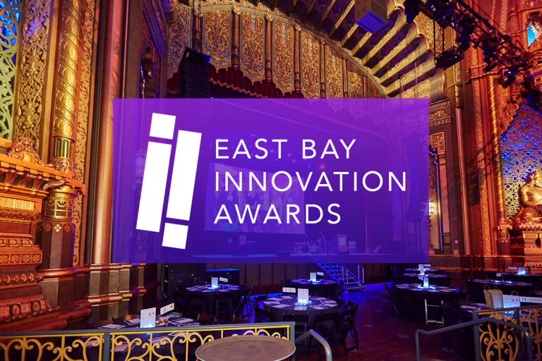 Photo of an ornate ballroom with a stage and tables with programs on them. On top, a purple rectangle with white text: East Bay Innovation Awards