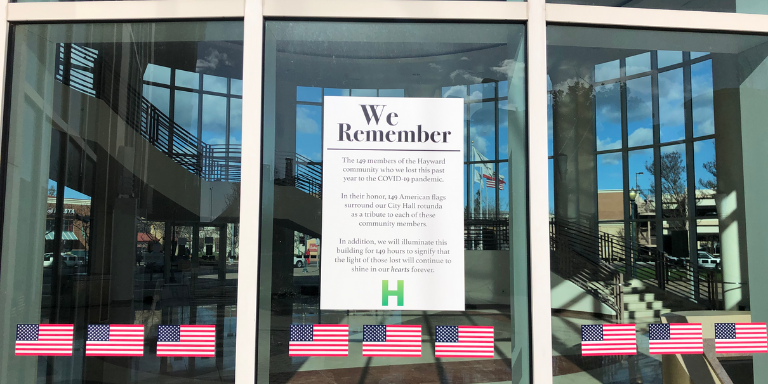"A row of American Flags underneath a ""We Remember""  Poster"