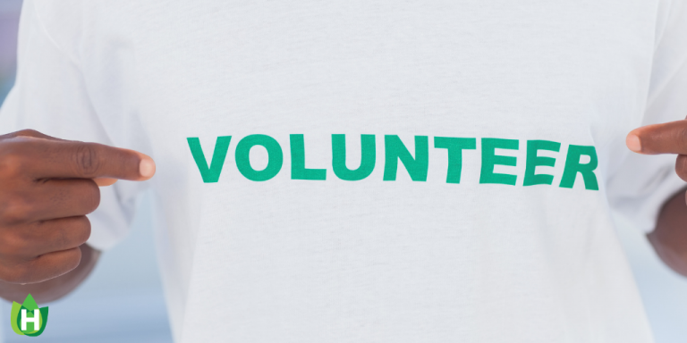 "A person wearing a white shirt with the word ""Volunteer"" in green across their chest"