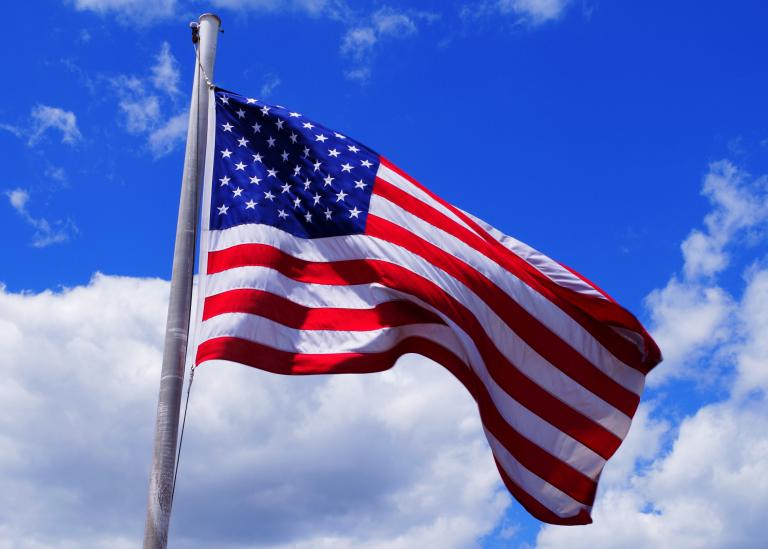 American flag against a bright blue sky with white cloud whisps