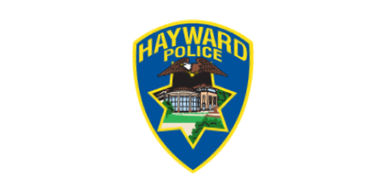 Hayward Police Logo in the shape of a blue badge with Hayward written across the top in yellow. An illustration of a Bald Eagle over an illustration of City Hall in the shape of a 7-point star is in the middle.