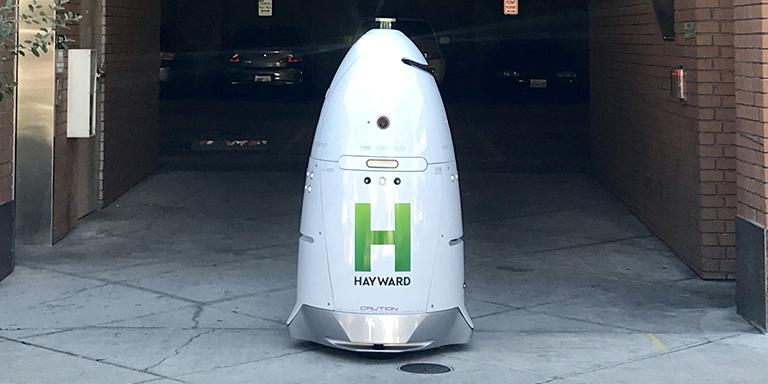 White Knighscope robot with green Hayward H outside of the Watkins Street Garage