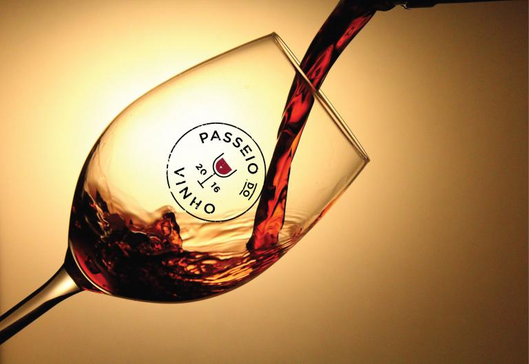 Red wine being poured into a glass with the Passeio do Vinho label
